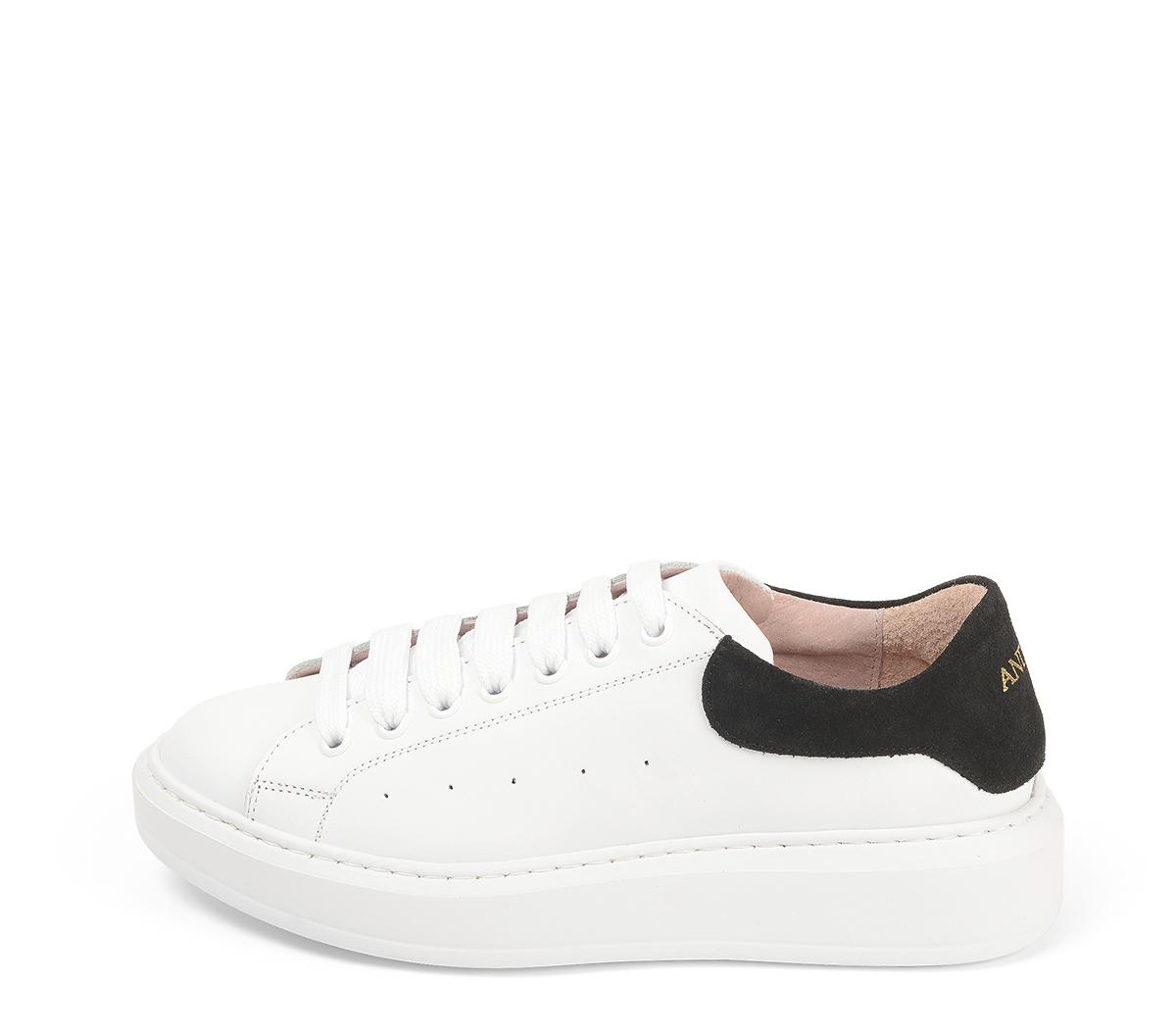 Ref. 4272 Sneaker piel blanca con detalle trasero en serraje negro. Cordones blancos. Altura plataforma trasera 3.5 cm y delantera de 2 cm.